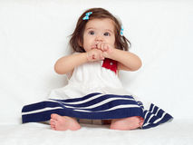 Happy little child girl sit on white towel, happy emotion and face expression, very surprised, the finger in mouth Royalty Free Stock Photography