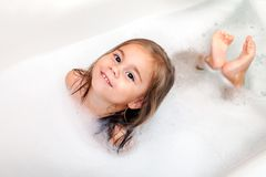 Happy little girl is taking a bath with a foam. Happy little child girl is taking a bath with a foam stock images