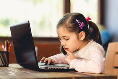 Happy Little Child Girl Using Laptop Computer and Typing on Keyboard royalty free stock photography
