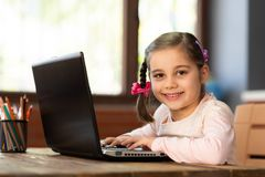 Happy Little Child Girl Using Laptop Computer and Typing on Keyboard. stock photo