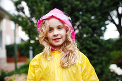 Happy little child girl in yellow raincoat. Royalty Free Stock Photos