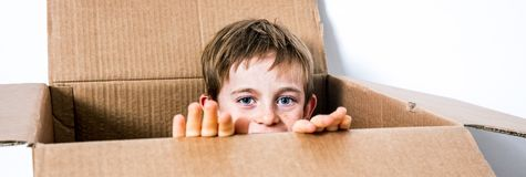 Happy little child hiding in a cardboard box, playing peekaboo. Happy little 6 year old child hiding his face in a cardboard box, playing peekaboo or hide and Stock Images