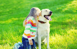 Happy little child with labrador retriever dog on grass Royalty Free Stock Photo