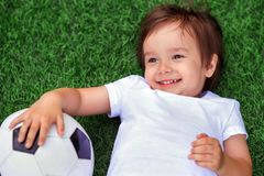 Happy little child laying on a green football field holding soccer ball and smiling. Future football star and little sportsman stock image