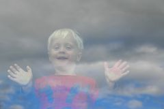Happy Little Child Looking Out the Window. View from outside the window, as a happy little boy has his hands and face pressed up the glass and is looking out Royalty Free Stock Photos