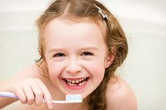 Happy little child  lost  primary tooth. Portrait of young girl sitting in the bath and cleaning her teeth Royalty Free Stock Images