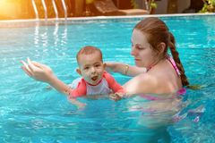 Happy little child with mother, Baby first time in a large pool and very impressed. Infant very happy, with open mouth, Teaching. To swim royalty free stock photos