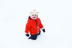 Happy little child in orange jacket plays in snow Stock Images