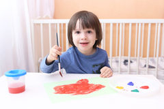 Happy little child painting with brush and gouache Royalty Free Stock Images
