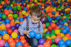 Happy little child playing at colorful plastic balls playground Stock Photos