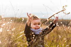 Happy little child playing on field Royalty Free Stock Images
