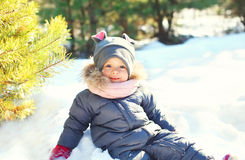 Happy little child playing sitting on snow in winter Royalty Free Stock Photo