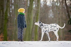 Happy little child, playing  in the snow with dog Royalty Free Stock Photo