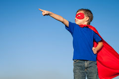 Happy little child playing superhero. Kid having fun outdoors. Concept of boy power royalty free stock photo