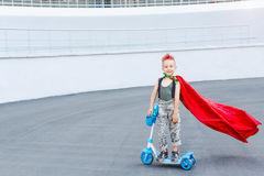 Happy little child playing superhero. Kid having fun outdoors. Kid superhero in a red cloak. The boy is riding a scooter. Royalty Free Stock Photo