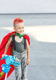 Happy little child playing superhero. Kid having fun outdoors. Kid superhero in a red cloak.A little boy with red hair. Royalty Free Stock Photo