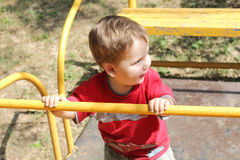 Happy little child plays on yellow swing Royalty Free Stock Images