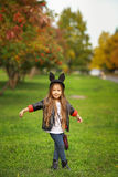 Happy little child posing for the camera, baby girl laughing and playing in the autumn on the nature walk outdoors. Stock Image