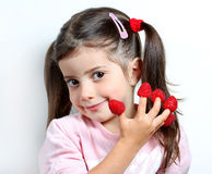 Happy little child with raspberries stacking on her fingers Royalty Free Stock Image