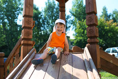 Happy little child screws up his eyes and sliding on playground Royalty Free Stock Photos