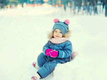 Happy little child sitting playing on snow in winter Stock Photography