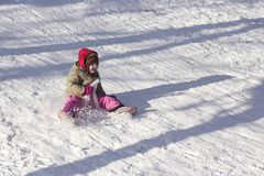 Happy little child sledging Stock Images