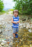 Happy little child standing in flashy river Royalty Free Stock Photo