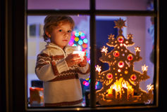 Happy little child standing by window at Christmas time and hold Royalty Free Stock Photos