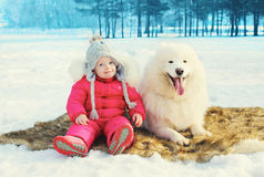 Happy little child with white Samoyed dog sitting on snow in winter Royalty Free Stock Images