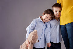 Happy little children, boys, hugging their mother at home, isola Stock Images