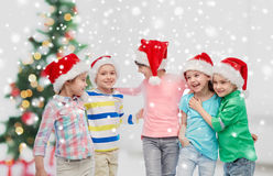 Happy little children in christmas santa hats Royalty Free Stock Image