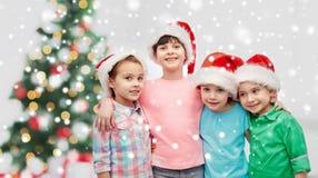Happy little children in christmas santa hats Royalty Free Stock Photos