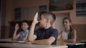 Happy little children in elementary school. Boys and girls study. Children raise hand up.  stock video footage
