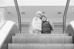 Happy little children on an escalator royalty free stock photo