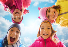 Happy little children faces over blue sky Stock Image