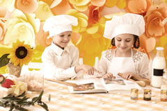 Happy little children in the form of a chef to prepare delicious Royalty Free Stock Photography