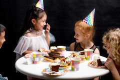 Happy little children having fun with cake during the party stock images