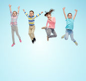 Happy little children jumping in air over blue Stock Photos