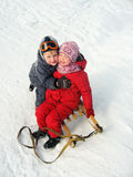 Happy little children are laughing in winter. Cheerful little boy and girl are laughing and hugging in the snow in winter outdoors Stock Images