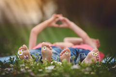 Happy little children, lying in the grass, barefoot, daisies aro Stock Photos