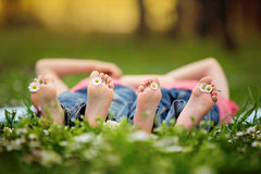 Happy little children, lying in the grass, barefoot, daisies aro Stock Images