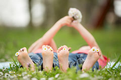 Happy little children, lying in the grass, barefoot, daisies around them royalty free stock photo