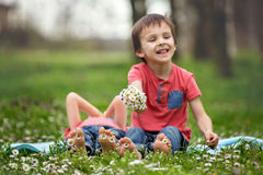Happy little children, lying in the grass, barefoot, daisies around them stock image