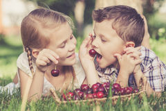 Happy little children lying near the tree with a basket of cherr Royalty Free Stock Photography