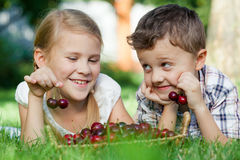 Happy little children lying near the tree with a basket of cherr Stock Photos