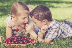 Happy little children lying near the tree with a basket of cherr Royalty Free Stock Images