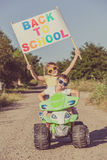 Happy little children playing on road at the day time. They driv Royalty Free Stock Images