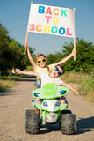 Happy little children playing on road at the day time. They driv Royalty Free Stock Photos