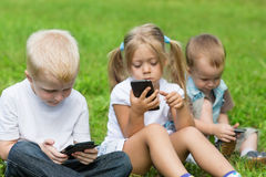 Happy little children playing in smartphones Stock Photos