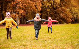 Happy little children running and playing outdoors Stock Photos